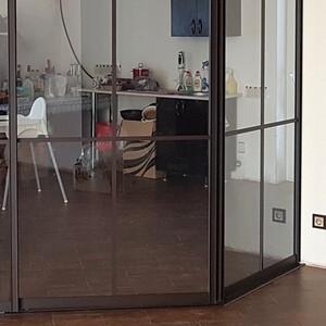 Раздвижная перегородка из прозрачного стекла с коричневым профилем